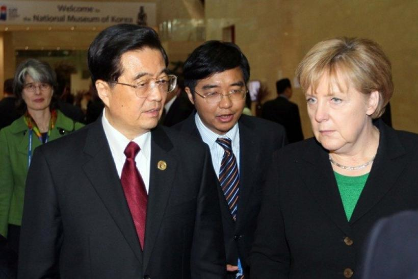 China's President Hu Jintao (L) talks with German Chancellor Angela Merkel as they arrive at the National Museum of Korea for dinner in Seoul November 11, 2010, on the first day of the G20 Summit. World leaders are gathering in Seoul on Thursday and Frida