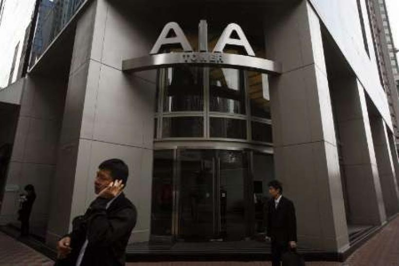 People walk past the AIA Tower, named after American International Assurance Co (AIA), in Hong Kong