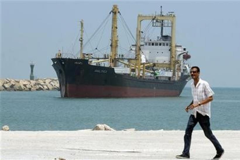 A man walks past Libyan-chartered ship Amalthea carrying aid for Palestinians in Gaza sailing in El Arish port,