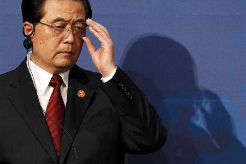 China's President Hu Jintao adjusts his glasses at the APEC CEO Summit in Yokohama