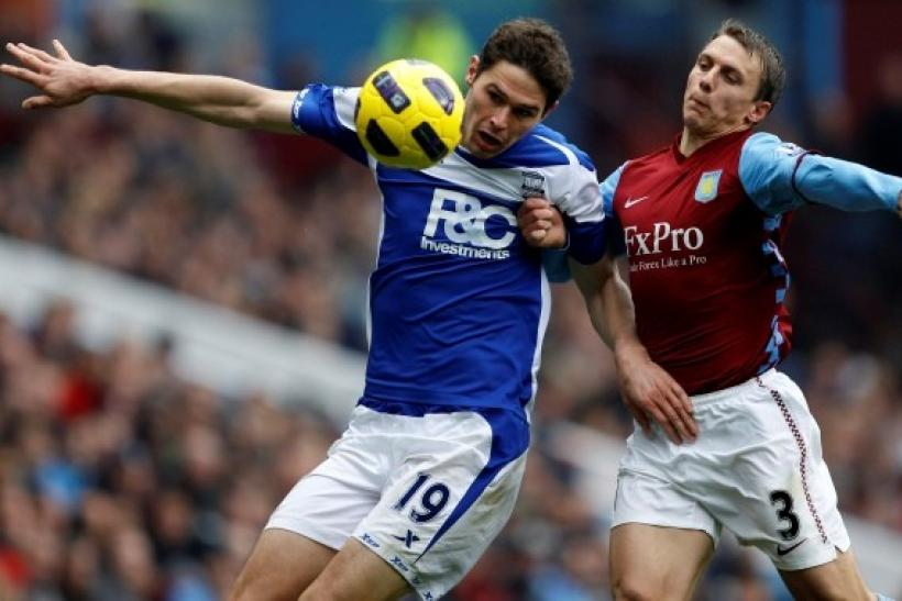 Aston Villa's Warnock challenges Birmingham City's Zigic during their English Premier League soccer match in Birmingham.