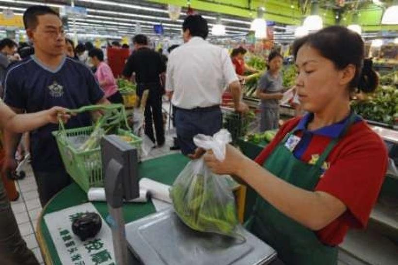A staff member packs a customer's items into a plastic bag at a supermarket in Changzhi, Shanxi province