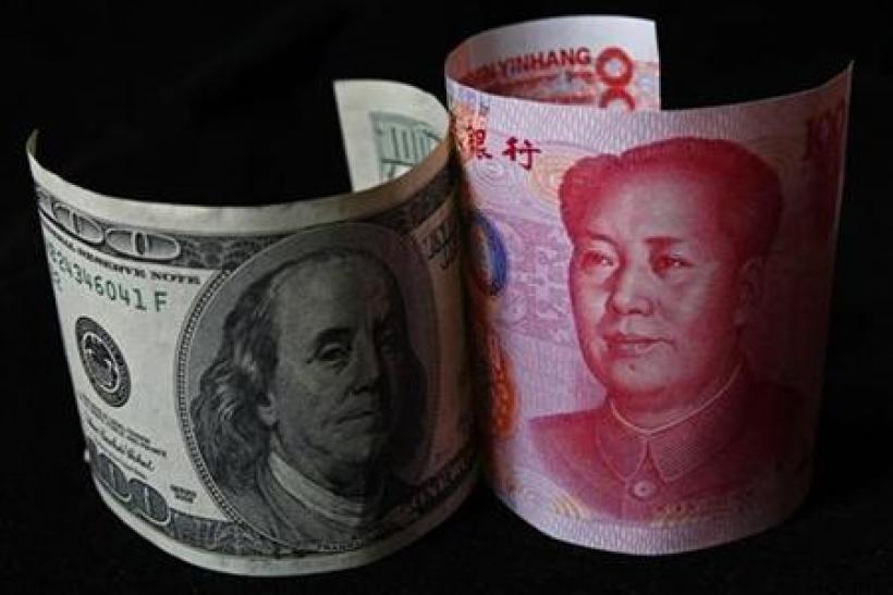 A 100 yuan banknote is placed next to a $100 banknote in this picture illustration taken in Beijing