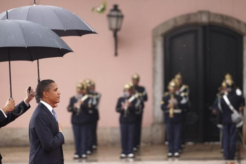 U.S. President Barack Obama and Portugal's President Anibal Cavaco Silva (partially hidden) are protected by umbrellas during an arrival ceremony at the Presidential Palace before the start of the NATO summit in Lisbon November 19, 2010.