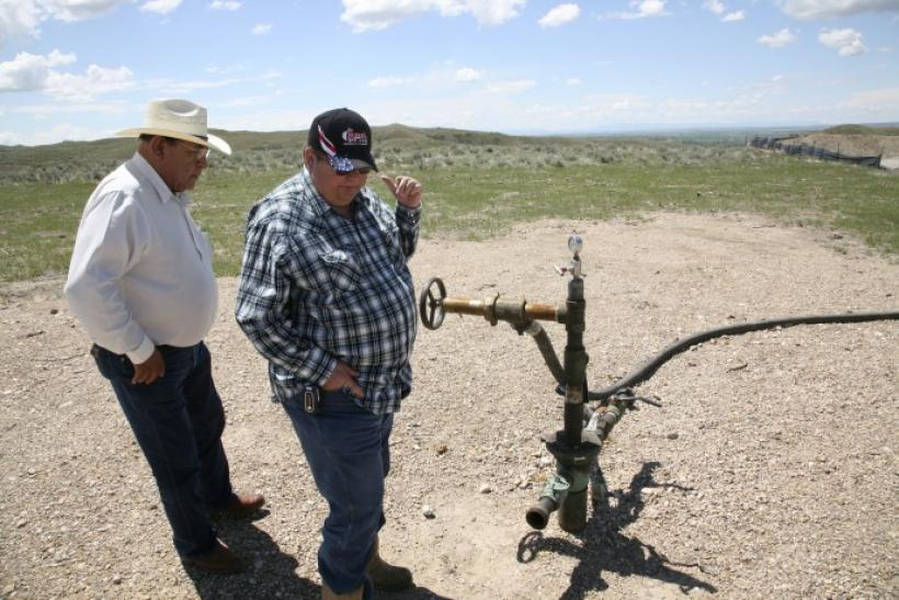 Two workers look at a gas well on the Crow Nation reservation near Crow Agency