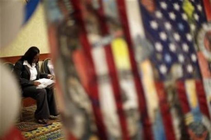 A woman fills out job application forms as she attends a job fair for military veterans and other unemployed people in Los Angeles, October 7, 2010.