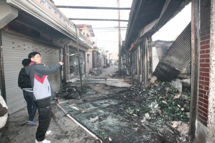 People stand beside houses, destroyed after they were hit by artillery shells fired by North Korea, on Yeonpyeong Island