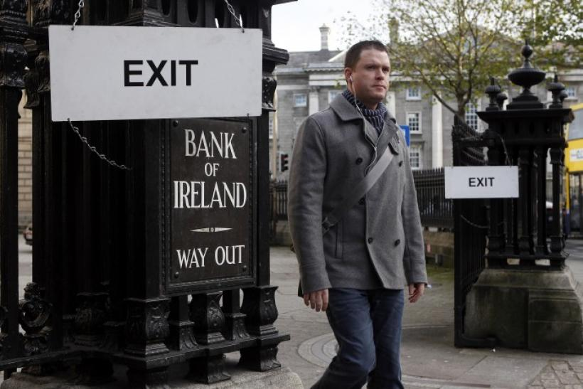 A pedestrian leaves the Bank Of Ireland headquarters in central Dublin