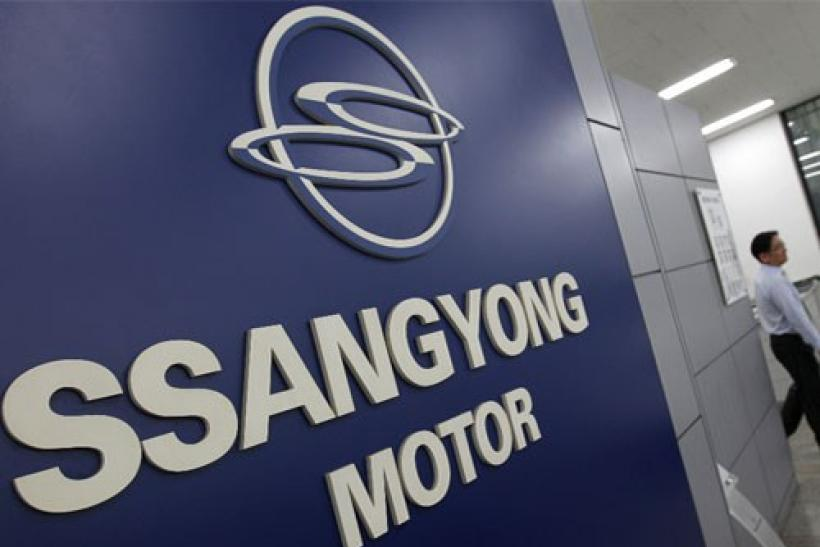 A salesperson from Ssangyong Motor walks past the company's logo at its branch shop in Seoul