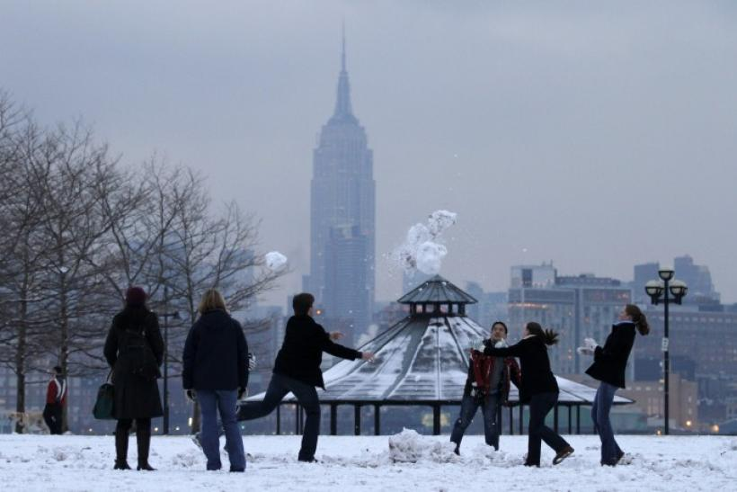 With New York's Empire State Building behind them, a group of friends play in the snow in a park along the Hudson River in Hoboken, New Jersey