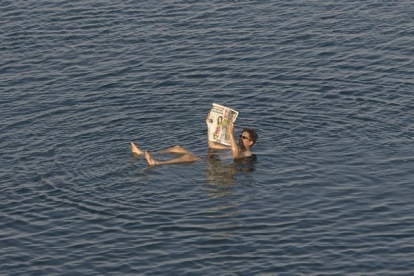 A tourist reads a newspaper as he floats in the Dead Sea resort of Ein Gedi May 20, 2010.