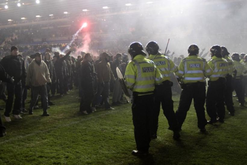 Birmingham City fans confront the police on the pitch after winning their English League Cup soccer match against Aston Villa in Birmingham.