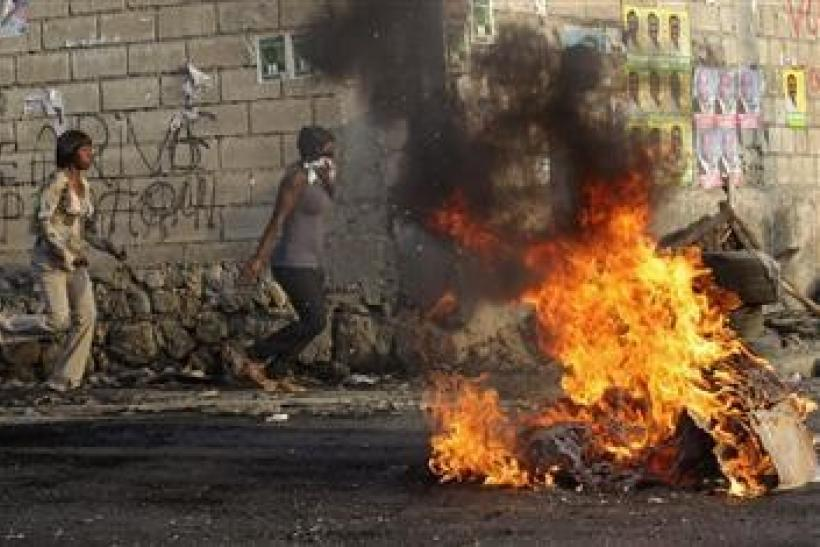 Haitians run on the street while tires burn during a protest in Port-au-Prince