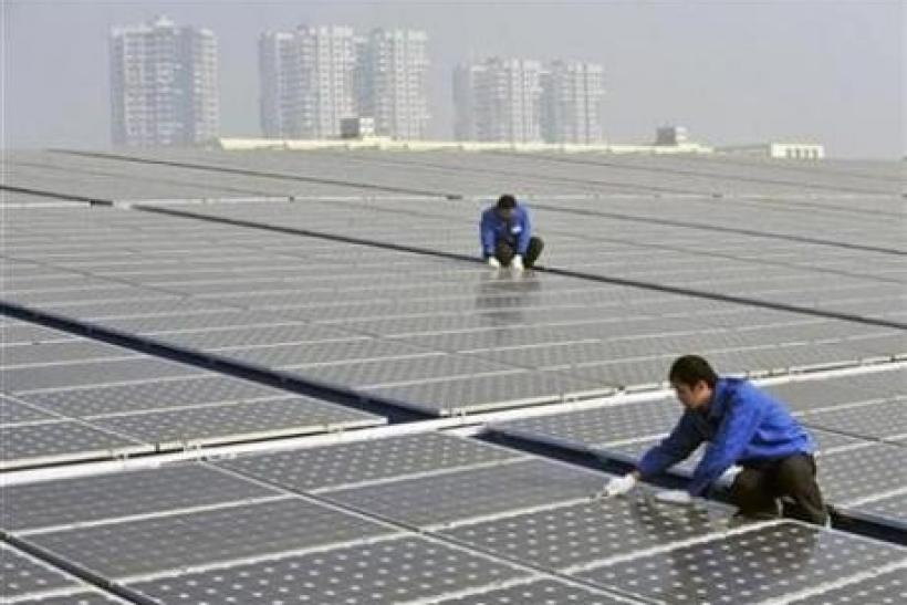 Technicians maintain solar panels on a roof at a solar power plant in Wuhan, Hubei province