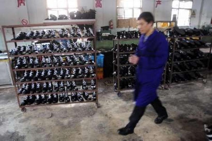 An employee walks in front of shelves with newly made shoes at a leather shoe factory in Hefei, Anhui province - file photo