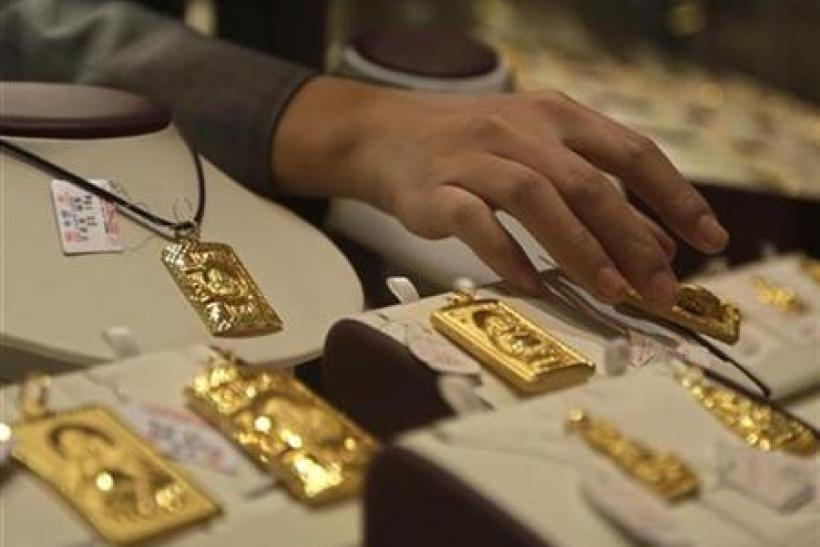 A sales assistant puts back a gold Buddha-shaped pendant after showing to a customer at Caibai Ornaments store in Beijing December 2, 2010.