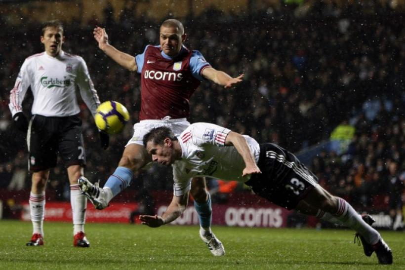 Liverpool's Carragher heads clear of Aston Villa's Young during their English Premier League soccer match in Birmingham on 29/12/2009.