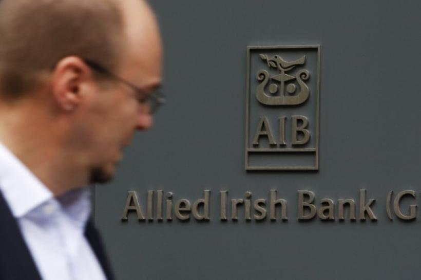 A pedestrian passes a branch of Allied Irish Bank in London