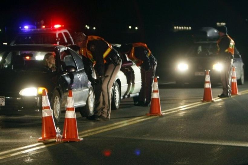 Jefferson County Sheriff Department officers ask drivers if they have been drinking while smelling for alcohol at a mobile Driving Under the Influence (DUI) checkpoint in Golden, Colorado.