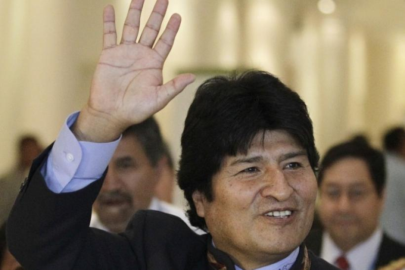 Bolivia's President Morales waves as he arrives to attend a plenary session at the Moon Palace, where climate talks are taking place, in Cancun