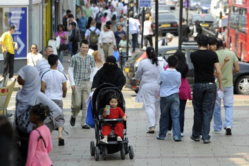 Shoppers walk in a market in the Upton Park neighborhood in east London