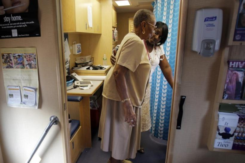 Healthcare educator Rainelle White (rear) checks the weight of client Norma Ferguson in the Family Van in Boston 09/08/2010