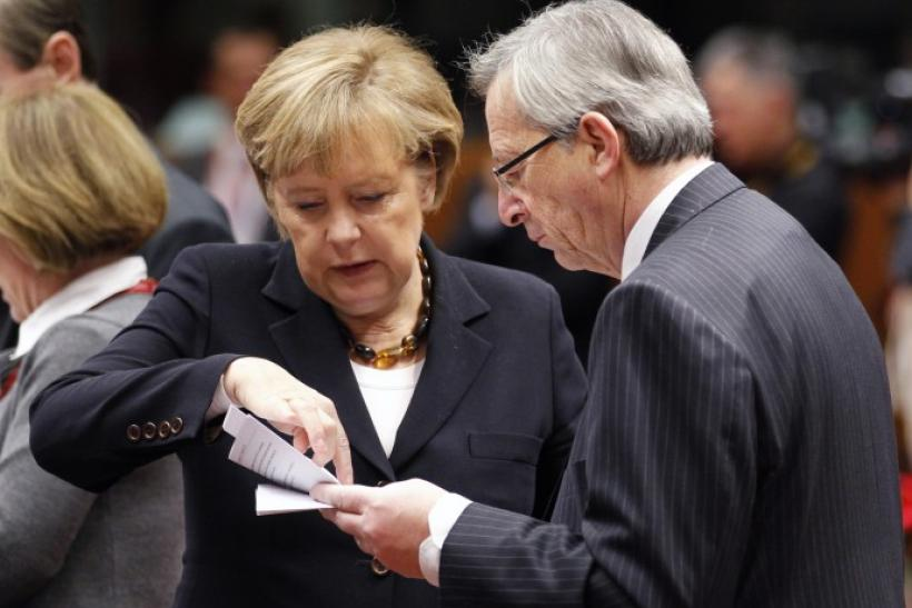 German Chancellor Merkel and Luxembourg's PM Juncker read a paper during an EU leaders summit in Brussels on Dec.17, 2010.