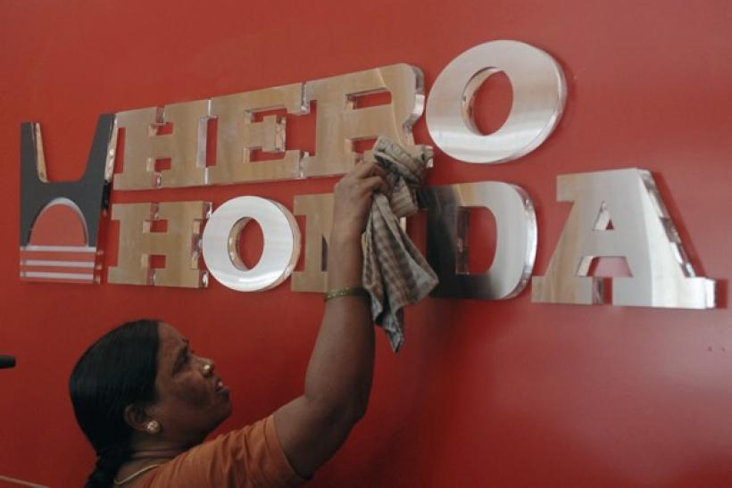 A worker cleans a Hero Honda logo inside its showroom in Hyderabad