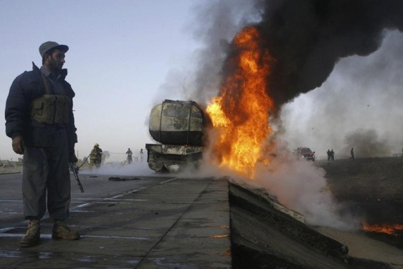 An Afghan policeman keeps watch next to a burning truck carrying fuel for NATO forces in Behsud district of Nangarhar province December 16, 2010.