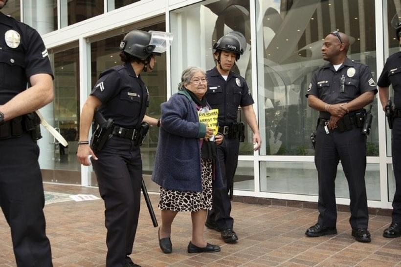 Julia Botello, 84 years old, is arrested for trespassing, along with 21 other protesters and homeowners facing foreclosure despite making payments under the Home Affordable Modification Program (HAMP).