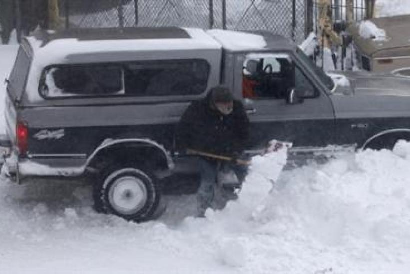 A truck stuck in a snow bank is shoveled out as blizzard-like conditions due to high winds continue in Hoboken