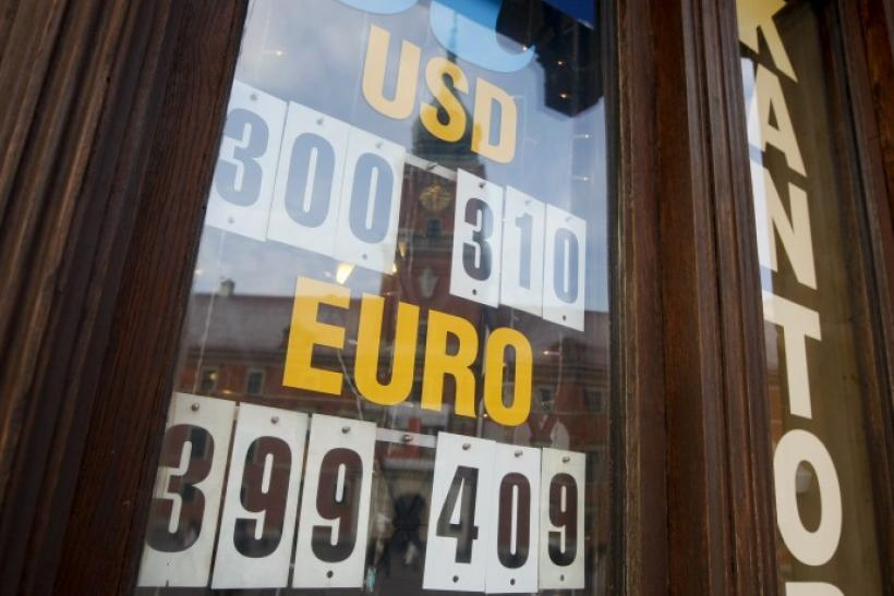 The currency exchange rates are displayed at an exchange office with the Royal Castle reflected in the window in Warsaw