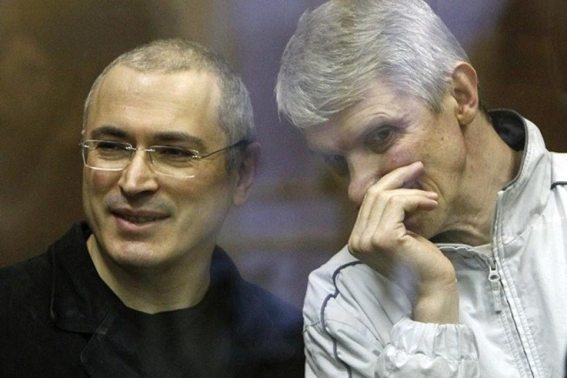 Jailed Russian former oil tycoon Mikhail Khodorkovsky and his business partner Platon Lebedev (R) stand in the defendants' cage before the start of a court session in Moscow December 28, 2010.