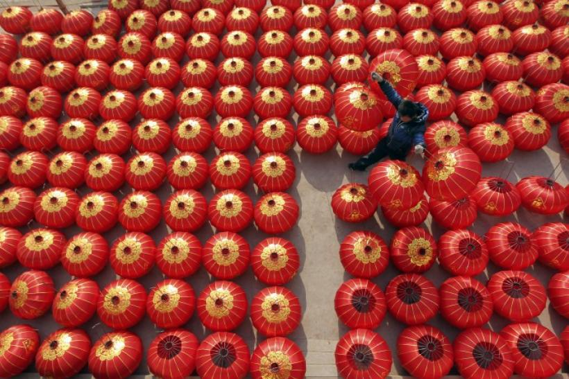 A worker lays out newly made red lanterns to dry at a lantern factory in Jishan county, Shanxi province