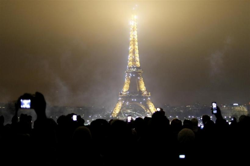 Revellers take snapshots of the Eiffel tower