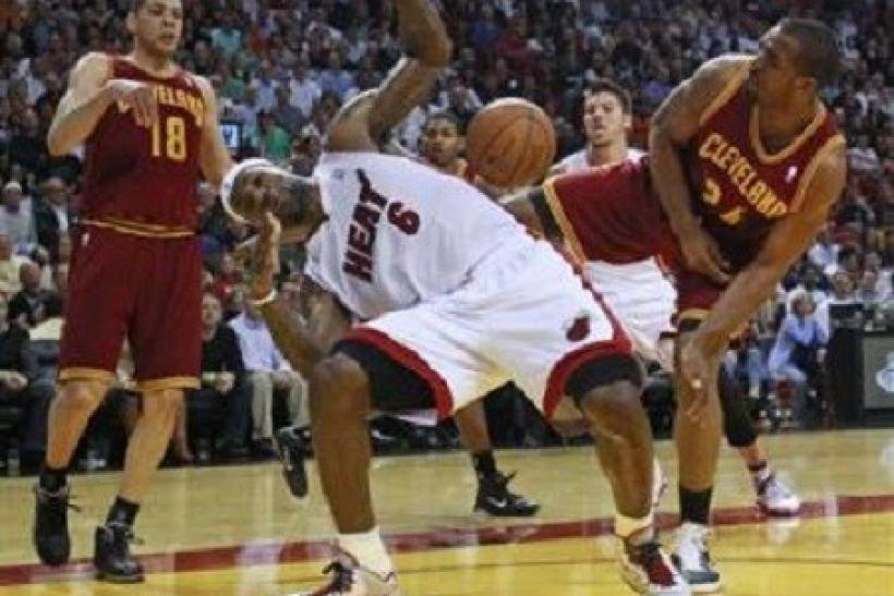 Miami Heat's LeBron James (C) is blocked by Cleveland Cavaliers Samardo Samuels (R) as Cavaliers Anthony Parker (L) looks on during first quarter NBA basketball action in Miami, Florida January 31, 2011.