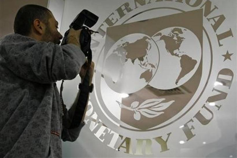 A photographer takes pictures through a glass carrying the International Monetary Fund (IMF)