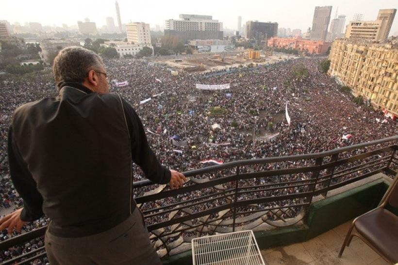 A man looks on as protesters take part in an anti-Mubarak protest at Tahrir Square in Cairo February 1, 2011. At least one million Egyptians took to the streets on Tuesday in scenes never before seen in the Arab nation's modern history, roaring in unison