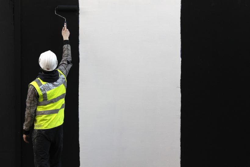 A worker paints a wall on a construction site in London