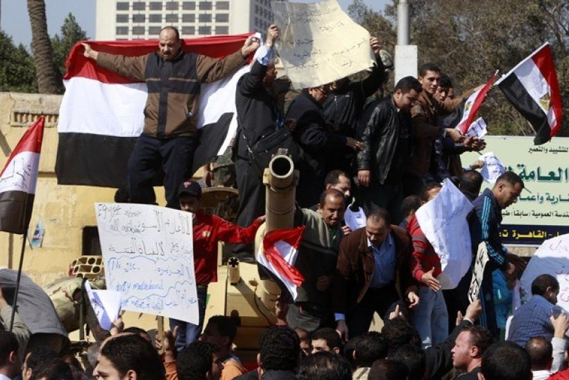 Pro-government supporters of Egyptian President Hosni Mubarak shout slogans atop an army tank near Tahrir square in central Cairo February 2, 2011.