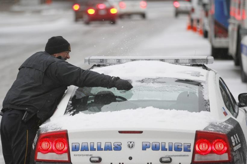 A Dallas police officer removes snow from his car after a storm front moved through Dallas