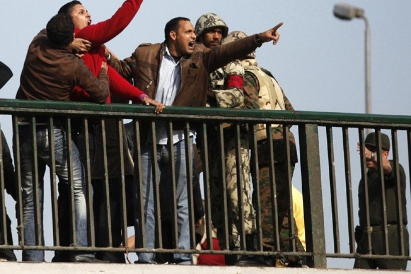 Pro-Mubarak supporters shout at opposition demonstrators as soldiers try to calm them down on a bridge near Tahrir Square in Cairo February 3, 2011.