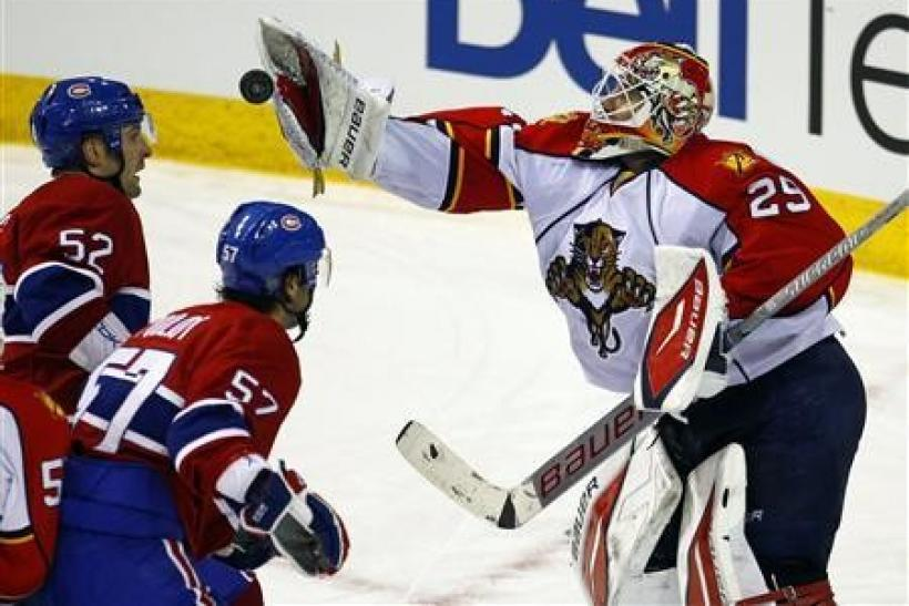 Florida Panthers goalie Tomas Vokoun (29) makes a save as Montreal Canadiens left wing Mathieu Darche (52) and left wing Benoit Pouliot (57) look for a rebound during the second period of their NHL hockey game in Montreal, February 2, 2011.