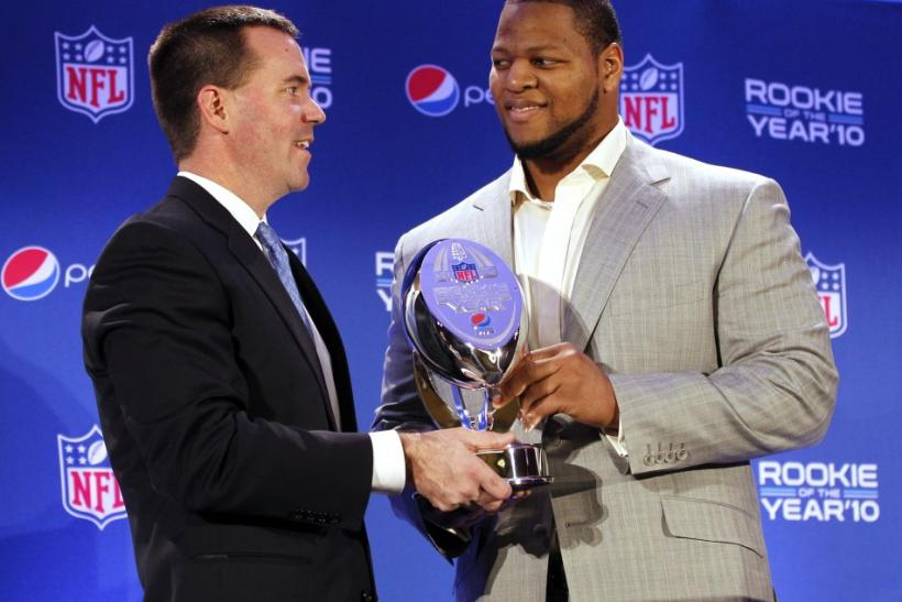 Ndamukong Suh (R) of the Detroit Lions holds the trophy as it was presented by Pepsi Vice President Jeff Dubiel at the Pepsi NFL Rookie of the Year at a news conference in Dallas, Texas, February 3, 2011.