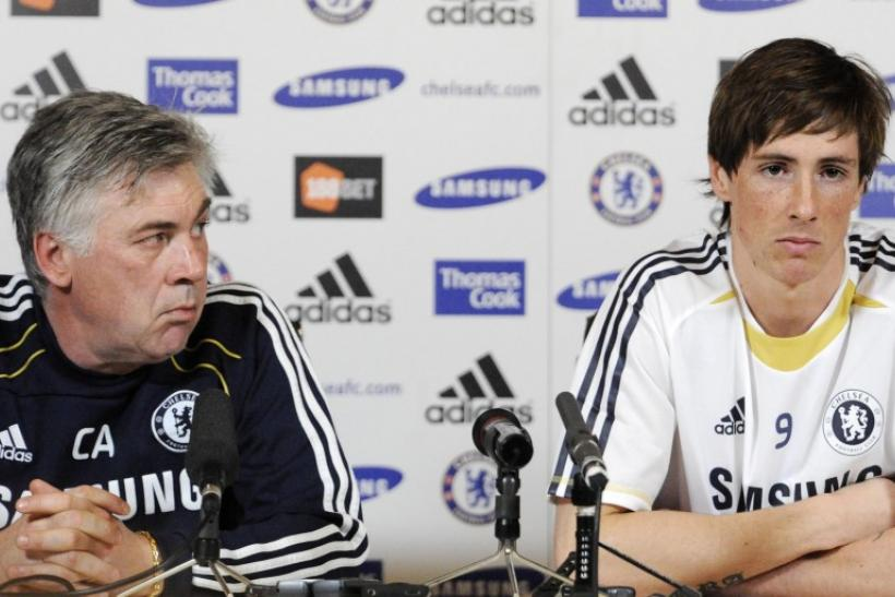 New Chelsea signing Torres listens to questions as he sits with manager Ancelotti during a news conference in Cobham.