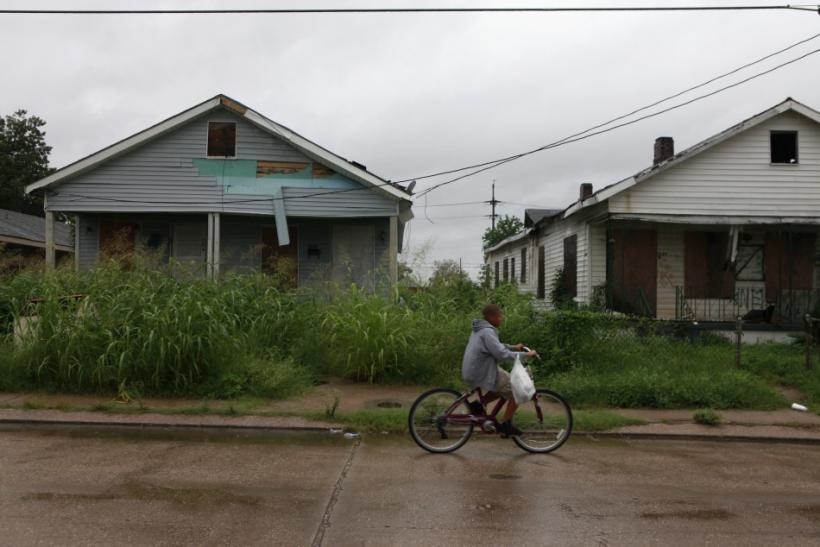 A boy bikes past homes unrepaired since Hurricane Katrina, on the eve of the storm's five year anniversary in the Lower Ninth Ward of New Orleans