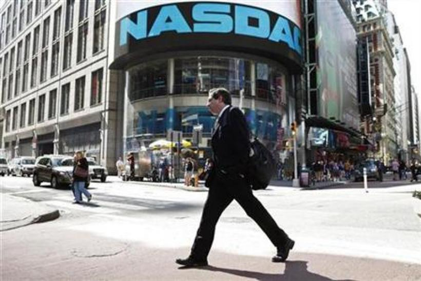 A pedestrian walks past the NASDAQ building in New York City