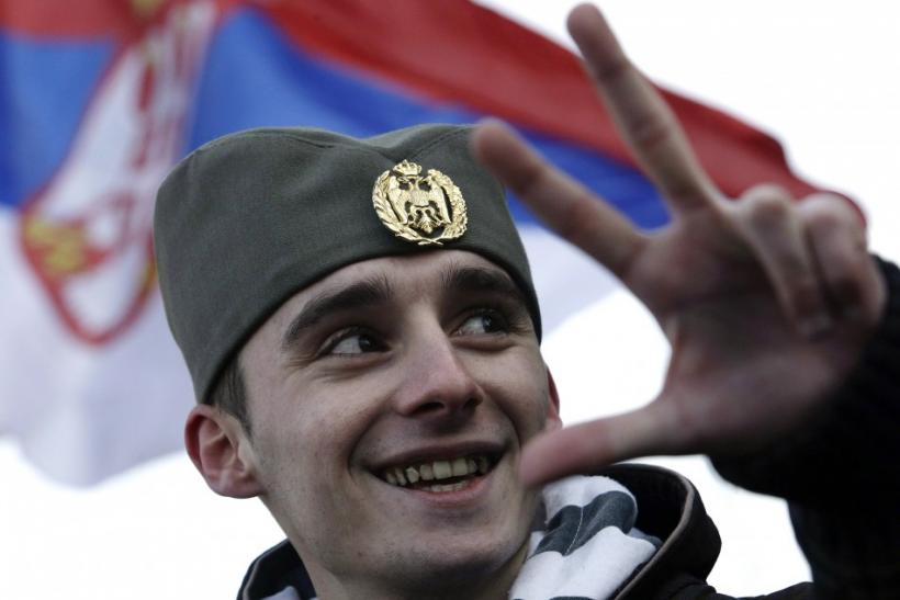 A protester wears traditional Serbian hat as he attends a rally in front of Serbian parliament building in Belgrade