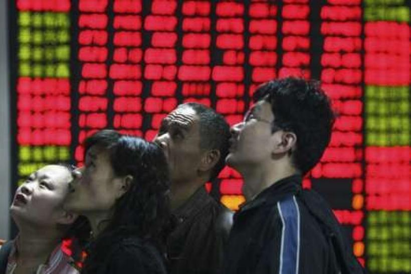 Investors look at an electronic board showing stock information at a brokerage house in Fuyang, Anhui province