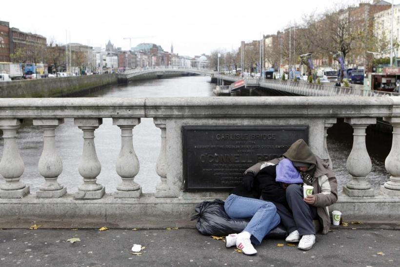 Homeless people beg for money on O'Connell bridge in central Dublin